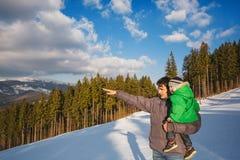 père portant son fils aux paysages d'hiver Photos stock