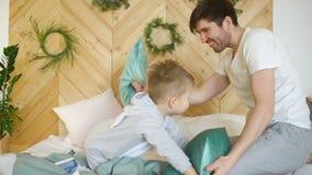 Père positif et fils ayant des piloows d'amusement et de combat sur le lit à la maison banque de vidéos