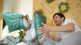 Père positif et fils ayant des piloows d'amusement et de combat sur le lit à la maison clips vidéos