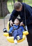 Père poussant le fils handicapé sur l'oscillation d'handicap Image stock