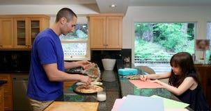 Père préparant la nourriture tandis que dessin de fille sur le papier dans la cuisine 4k banque de vidéos