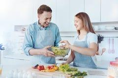 Père rayonnant et enfant féminin faisant la salade ensemble Photo stock