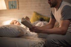 Père Reading Bedtime Story au fils image stock