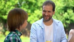 Père regardant avec fierté le fils, temps de dépense ensemble, extérieur de dîner de famille photo stock