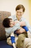 Père retenant le fils handicapé Photos stock