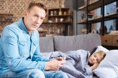 Père sérieux vérifiant la température de son fils malade Photographie stock
