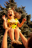 Père se soulevant vers le haut de rire la petite fille Image stock