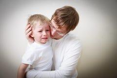 Père soulageant son petit fils pleurant photographie stock libre de droits