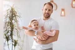 Père sportif tenant l'enfant en bas âge dans des ses bras à la maison Photographie stock libre de droits