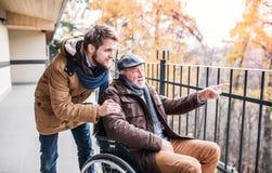 Père supérieur dans le fauteuil roulant et le jeune fils sur une promenade Photographie stock libre de droits