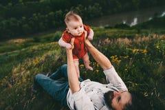 Père supportant le bébé se trouvant sur la famille heureuse extérieure d'herbe photographie stock libre de droits