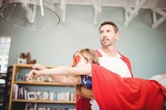 Père tenant la fille avec le costume de super héros Image libre de droits