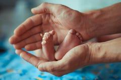 Père tenant le petit pied de son fils photographie stock libre de droits