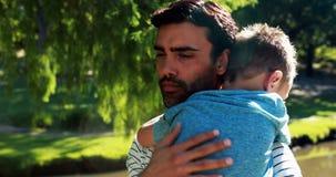 Père tenant son fils de sommeil en parc banque de vidéos