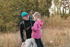 Père trimardant avec l'enfant sur le sac à dos photos stock