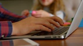 Père utilisant l'ordinateur portable tandis que fille jouant avec de l'argile dans le salon banque de vidéos