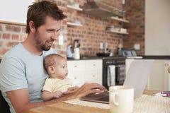 Père Working From Home sur l'ordinateur portable avec le fils de bébé images libres de droits