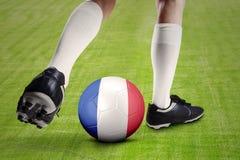 Pé da bola do jogo do jogador de futebol com uma bandeira de França Imagem de Stock Royalty Free