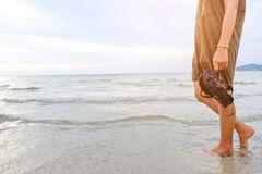 Pé da jovem mulher que anda ao longo da onda da água do mar e da areia na praia na ilha tropical com atitude despreocupada e rela fotos de stock