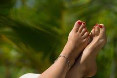 Pé da mulher com o pedicure vermelho na praia tropical im conceptual Fotografia de Stock Royalty Free