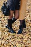 Pé da mulher entre as folhas amarelas no parque colorido do outono fotografia de stock royalty free