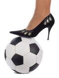 Pé da mulher na esfera de futebol Fotografia de Stock