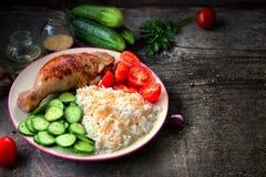 Pé de galinha grelhado, arroz branco, pepino slised com sementes de sésamo, tomtoes e ervas imagens de stock