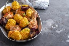 Pé de galinha Roasted com batatas cominhos e alho no fundo preto Copie o espaço fotografia de stock