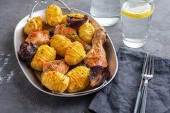 Pé de galinha Roasted com batatas cominhos e alho no fundo preto Copie o espaço imagens de stock
