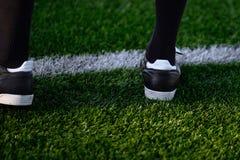Pé de um jogador de futebol ou do jogador de futebol na grama verde Foto de Stock Royalty Free