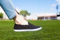 Pé de uma menina atlética nova e um gramado de um campo de futebol Imagem de Stock Royalty Free
