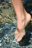 Pé descalço do ` s da mulher na água fria fresca imagem de stock