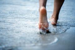 Pé desencapado da mulher que anda na praia do verão feche acima do pé da jovem mulher que anda ao longo da onda da água do mar e  imagem de stock