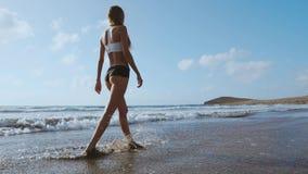 Pé desencapado da mulher que anda na praia do verão feche acima do pé da jovem mulher que anda ao longo da onda da água do mar e  vídeos de arquivo