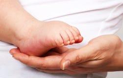 Pé do bebê na mão da matriz Fotografia de Stock
