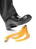 Pé do homem de negócios em uma casca da banana Fotografia de Stock Royalty Free