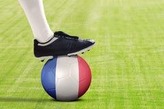 Pé do jogador de futebol com a bola no campo Imagem de Stock Royalty Free
