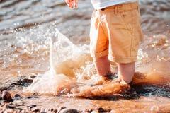 Pé do menino no rio A água espirra imagem de stock