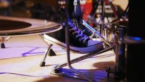 Pé do ` s do baterista nas sapatilhas que movem o pedal do baixo do cilindro filme