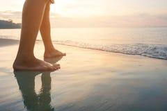 Pé dos homens novos que andam ao longo da onda da água do mar e da areia na praia na ilha tropical foto de stock