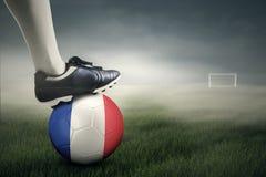 Pé e uma bola de futebol no campo Imagens de Stock Royalty Free