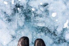 Pé humano nas sapatas no gelo do Lago Baikal Fotos de Stock