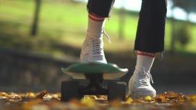 Pé humano nas sapatilhas brancas em um close-up do skate O pé em uma sapatilha branca aumenta um skate no fundo de filme