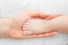 Pé recém-nascido do bebê na mão da mãe Puericultura, amor, proteção Fotografia de Stock