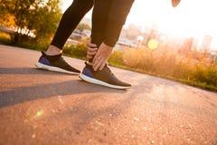 Pé tocante do corredor atlético do homem na dor devido ao tornozelo torcido Foto de Stock Royalty Free