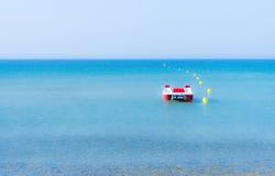 Pédalo rouge et blanc sur une mer bleue calme, près des balises jaunes Photographie stock libre de droits