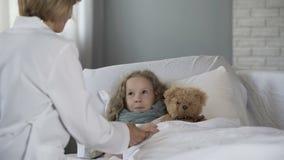 Pédiatre aimable examinant la petite fille malade à la maison, docteur soulageant l'enfant malade clips vidéos