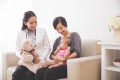 Pédiatre féminin asiatique montrant une poupée au bébé dans le mot Image stock