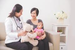 Pédiatre féminin asiatique montrant une poupée au bébé dans le mot Images stock