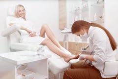 Pédicure faisant la procédure le pied de sourire de clients image stock